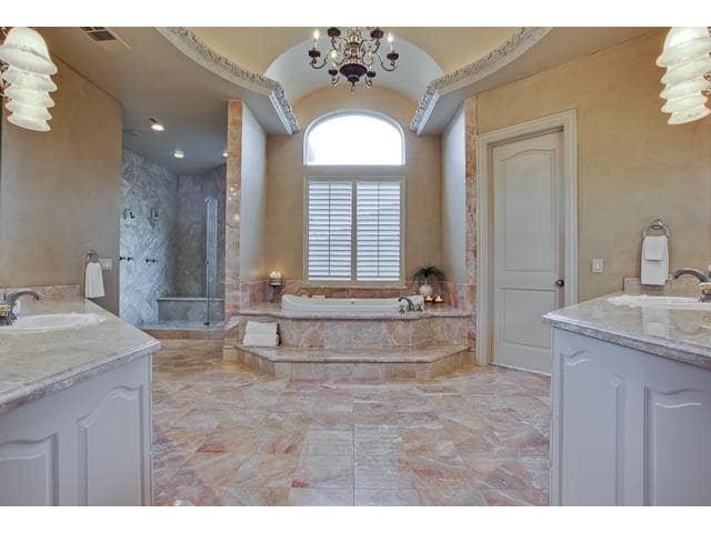 Primary bathroom with a walk-in shower, drop-in bathtub, and two sink vanities.