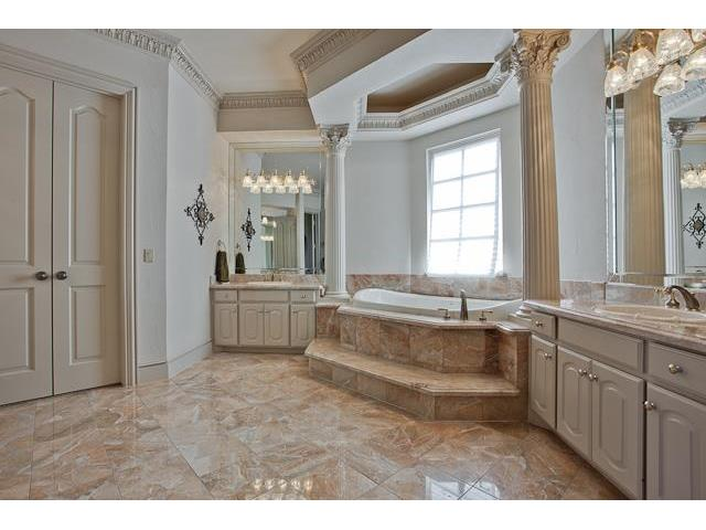 This bathroom has a deep soaking tub, his and her vanities, and a walk-in closet resting behind the double door.