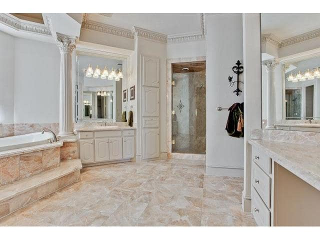 A walk-in shower enclosed in a hinged glass door complete this bathroom.