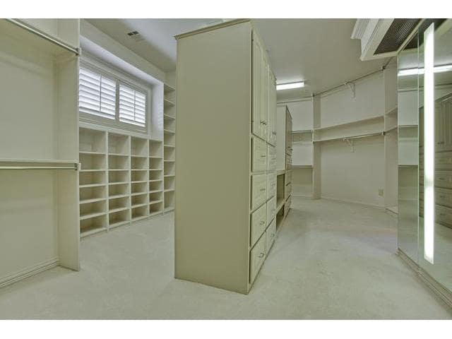 A spacious walk-in closet filled with built-in shelves, cream cabinets, and floor-to-ceiling mirror.