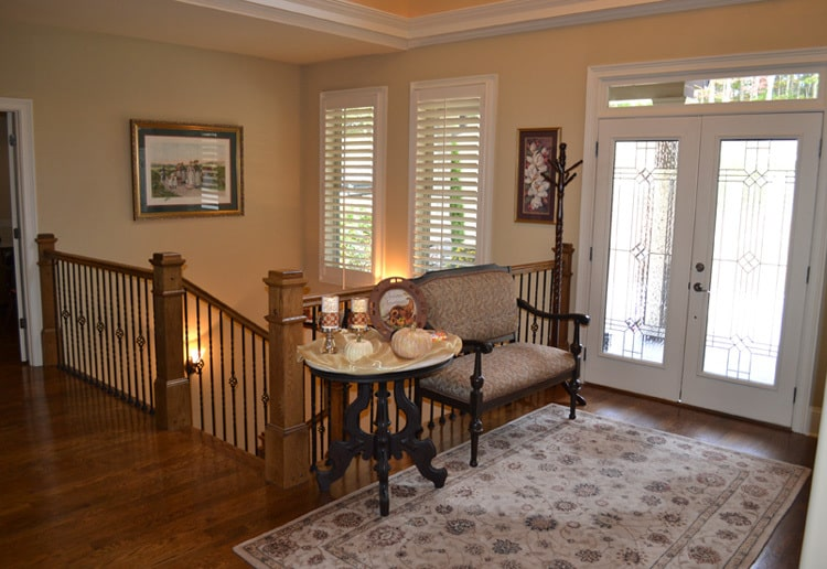 The foyer has a french entry door, an upholstered bench, round side table, and a floral area rug.