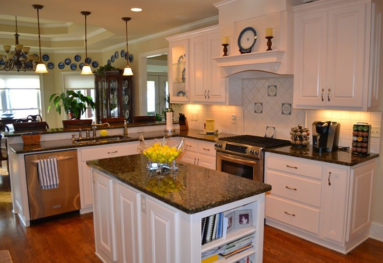 The kitchen is equipped with black granite countertops, stainless steel appliances, white cabinetry, center island, and a snack bar.