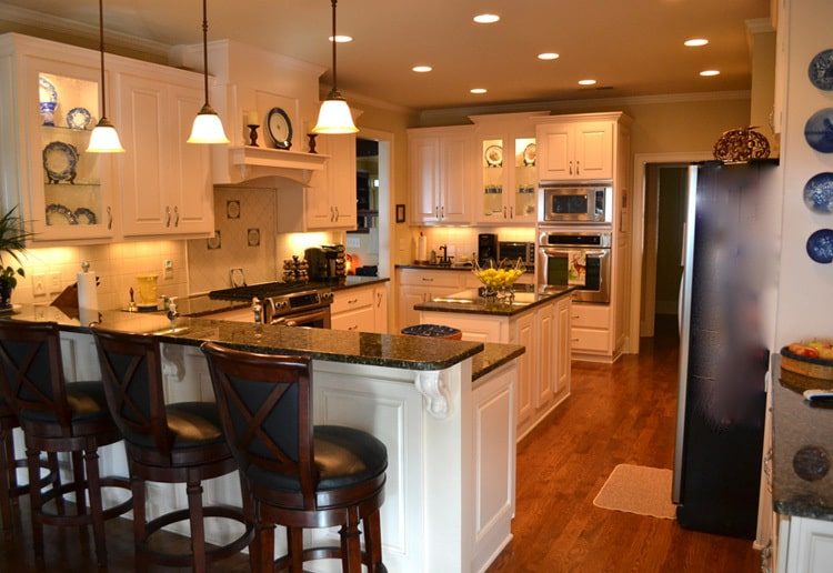 Small glass pendants along with recessed ceiling lights create a cozy ambiance in the kitchen.