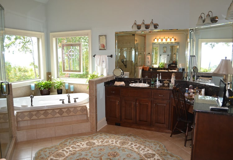 More vanities and a corner bathtub under the picture windows complete the primary bathroom.
