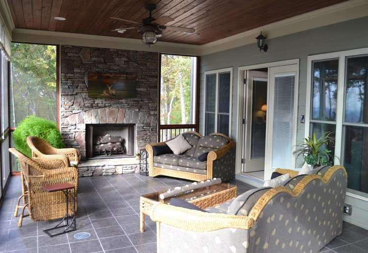Screened porch with a stone fireplace, patterned sofas, wicker armchairs, and a matching coffee table.