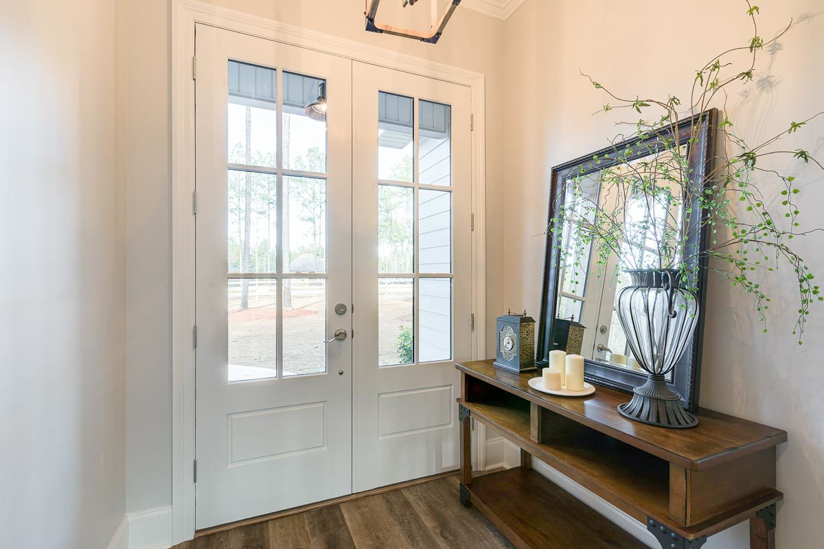 Foyer with a french front door and a wooden console table topped by a large framed mirror, candle holders, and an iron glass vase.