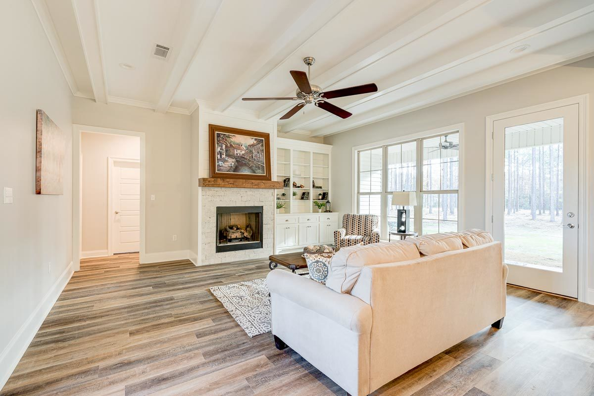 The living room has a beamed ceiling, a glass-enclosed fireplace, a patterned armchair, and a beige sofa.