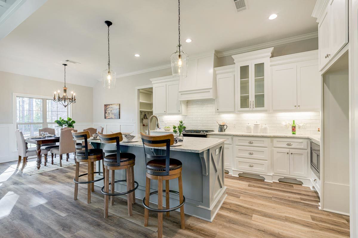 Eat-in kitchen with white cabinetry, breakfast island, and a rectangular dining set.