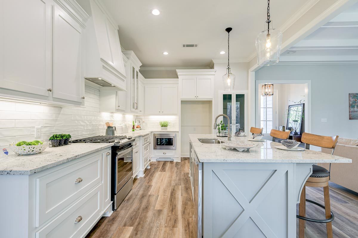 Stainless steel appliances, marble countertops, and white subway tile backsplash complete the kitchen.