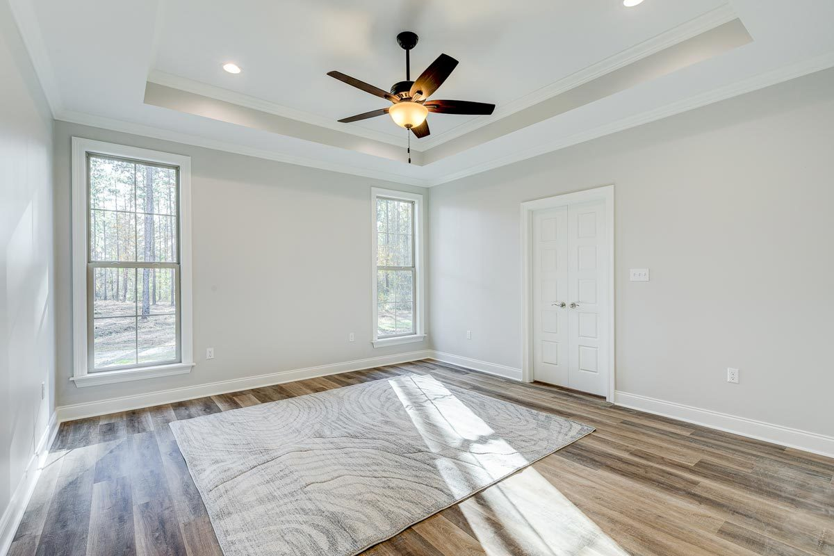 The primary bedroom has a tray ceiling and a natural hardwood flooring topped by a patterned rug.