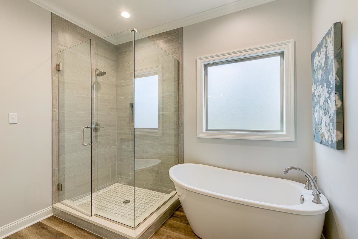 Primary bathroom with a walk-in shower and a freestanding tub placed under the picture window.