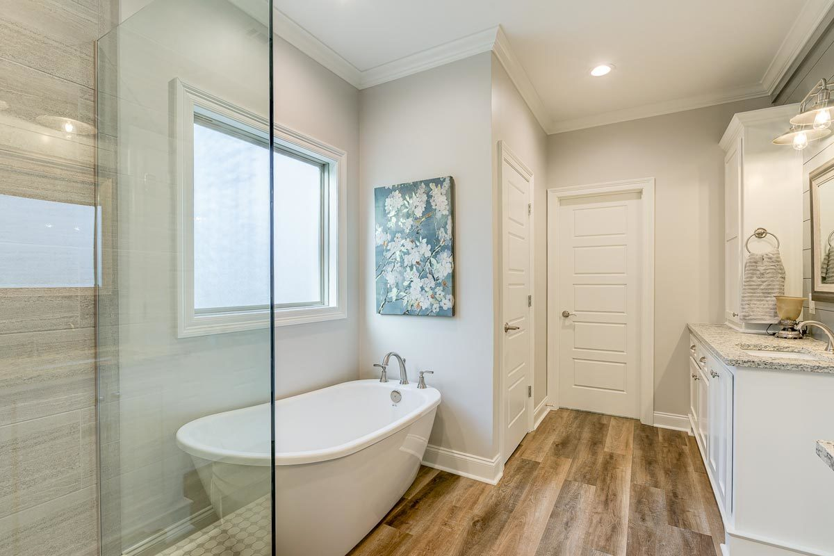 The primary bathroom has wide plank flooring and light gray walls adorned with floral artwork.