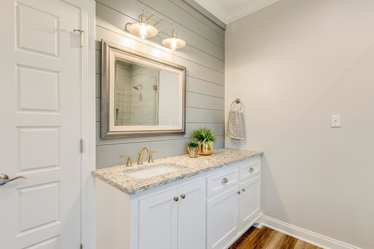 White vanity paired with a framed mirror and dome sconces.