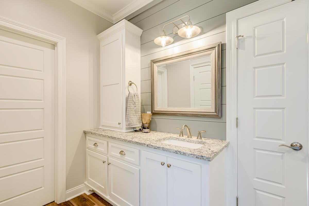 Another vanity with granite countertop and white cabinets.