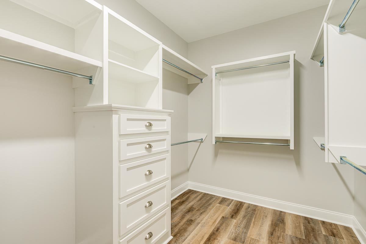The walk-in cabinet is filled with white drawers, built-in shelves, and pole racks.