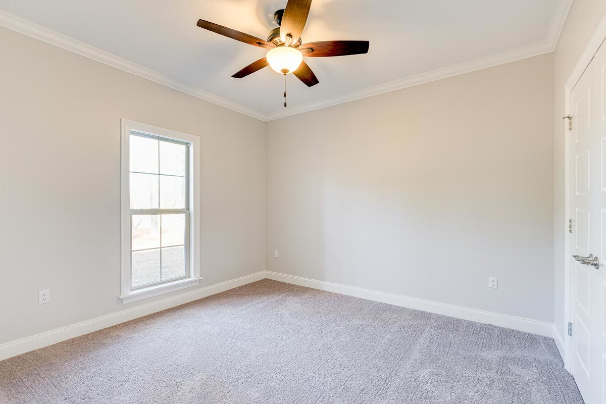 This bedroom has a white framed mirror, beige carpet flooring, and a regular ceiling mounted with a ceiling fan.
