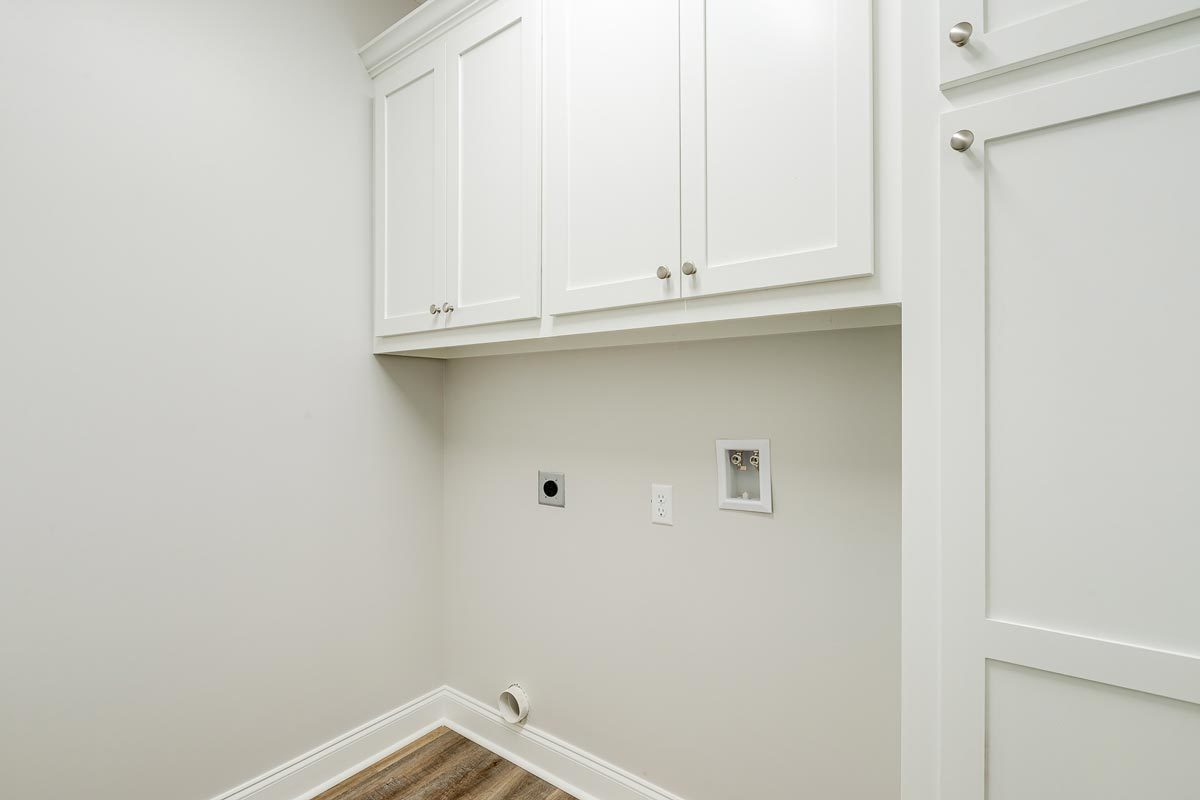 The utility has white cabinets that blend in with the walls lined with white base molding.