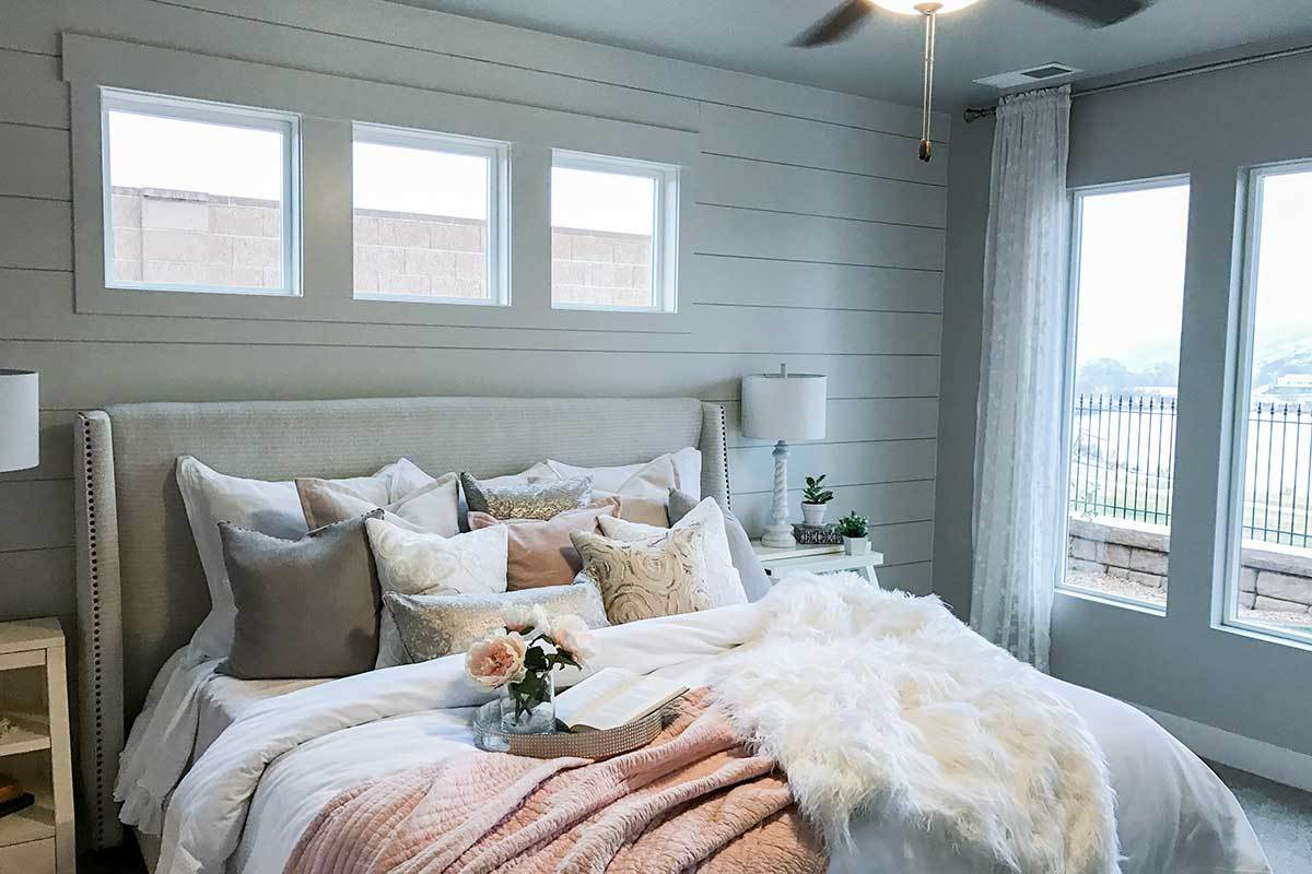 The primary bedroom has white nightstands, a gray upholstered bed, and a shiplap accent wall fitted with glass windows.