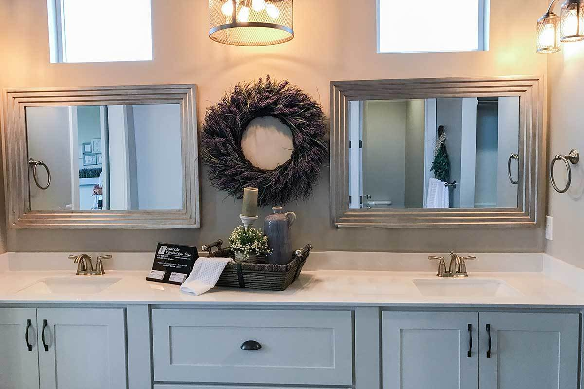 A pair of framed mirrors flanking a wreath hang above the dual sink vanity.