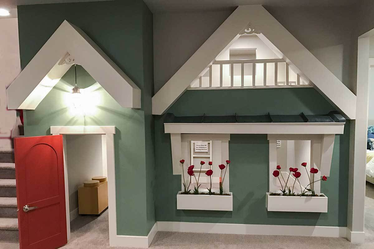 Kids' playroom showcasing a red front door, green walls, planter boxes, and gable rooflines.