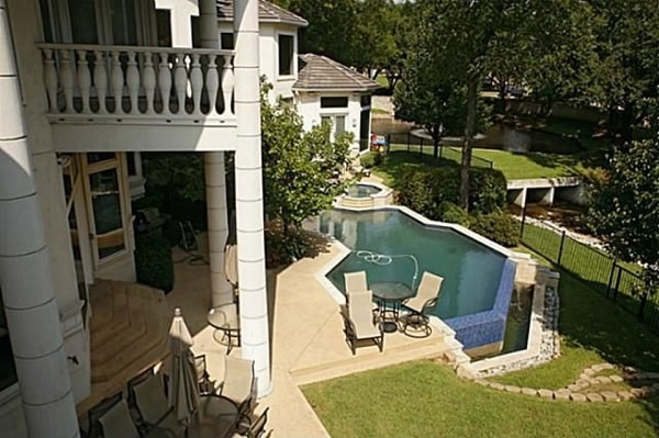 Rear exterior view with upper balcony, covered lanai, and a swimming pool with spa.