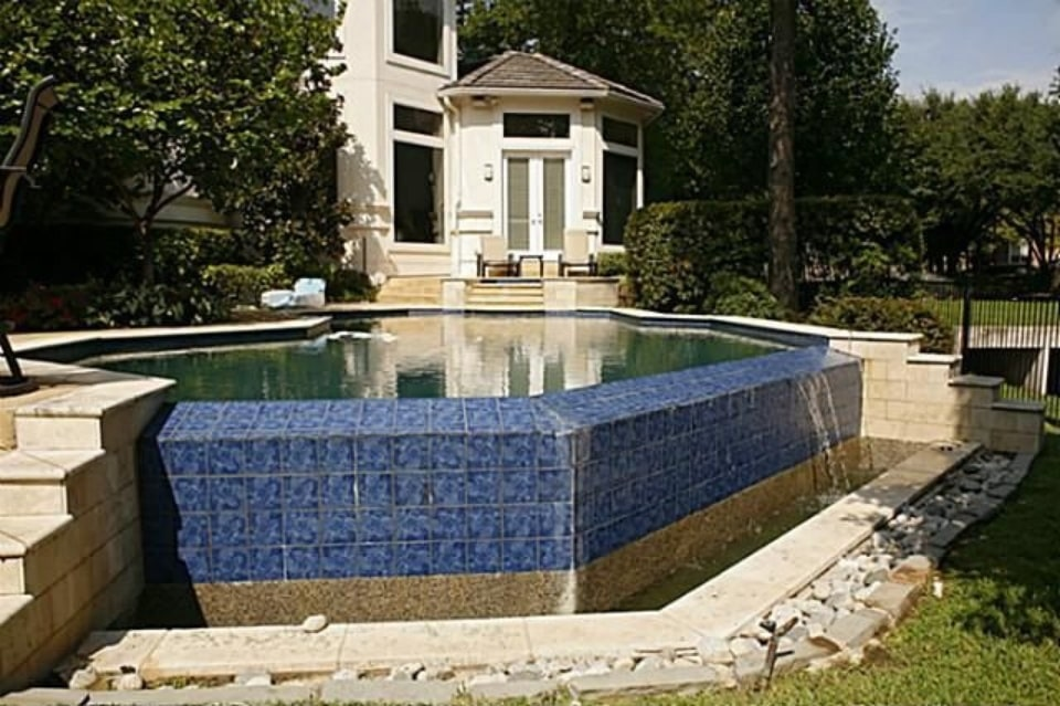 A closer look at the swimming pool with tiled staircases and a water feature.