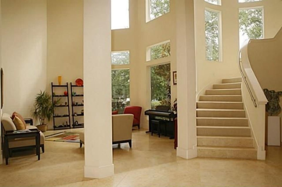The foyer has a staircase and a towering column defining the living room.