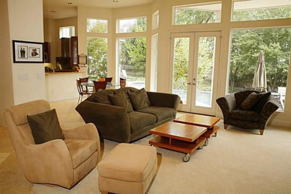 Family room with velvet seats, mobile coffee tables, and a french door that leads out to the back porch.