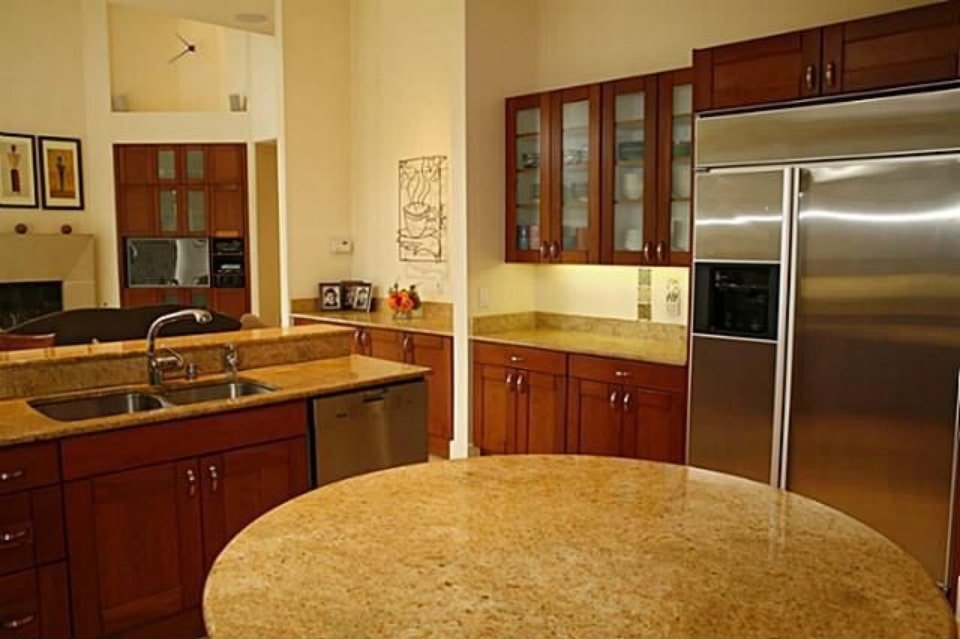 The kitchen is equipped with granite countertops, stainless steel appliances, and a double bowl sink fitted on the two-tier peninsula.