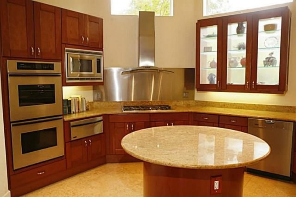 Wooden cabinets match the center island that's crowned by a round granite countertop.