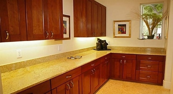 The butlery is filled with wooden cabinetry and beige granite countertops.