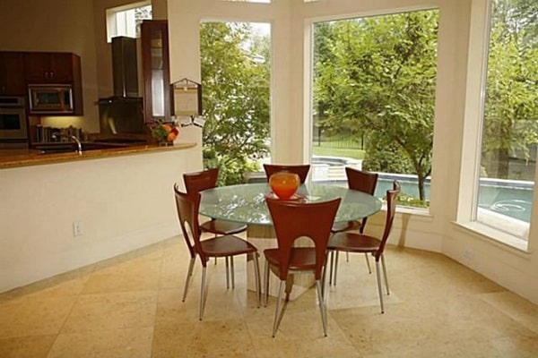 The breakfast nook with a round dining set is situated near the bay window overlooking the backyard pool.