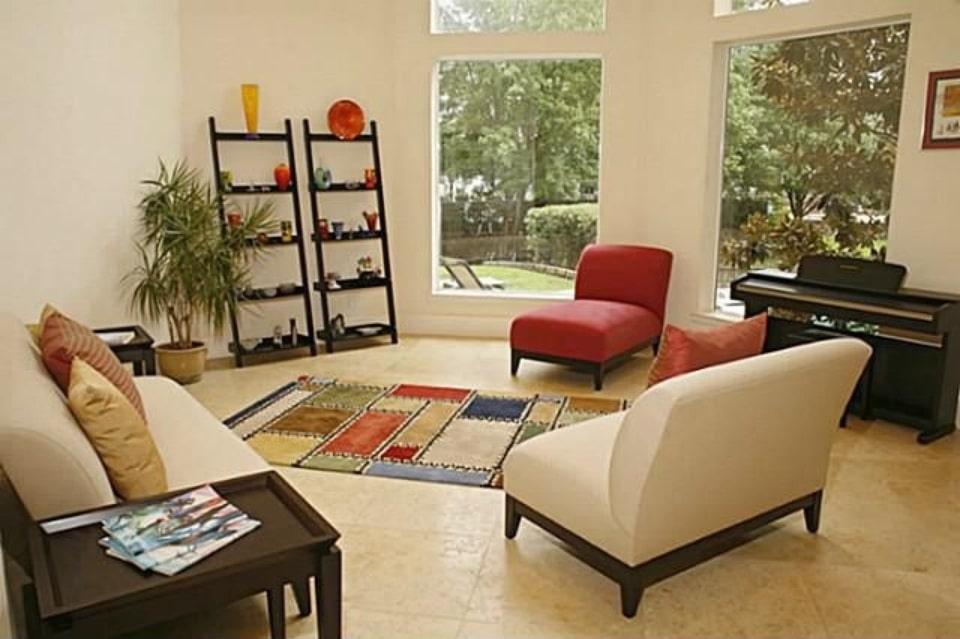 Living room with cozy seats, black shelving units, piano, and a multicolored area rug.