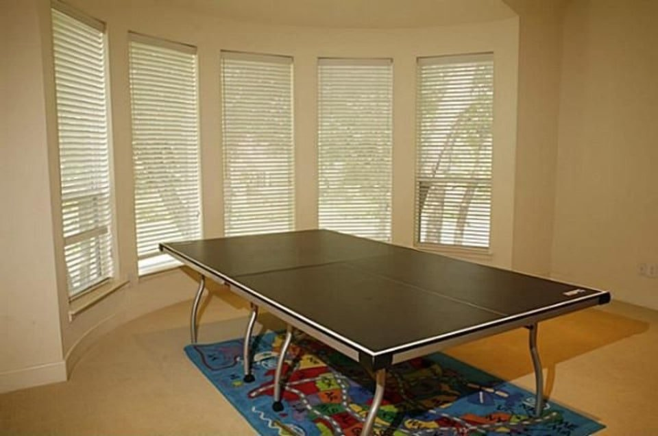 Game room with a bay window and a black table sitting on a blue printed rug.