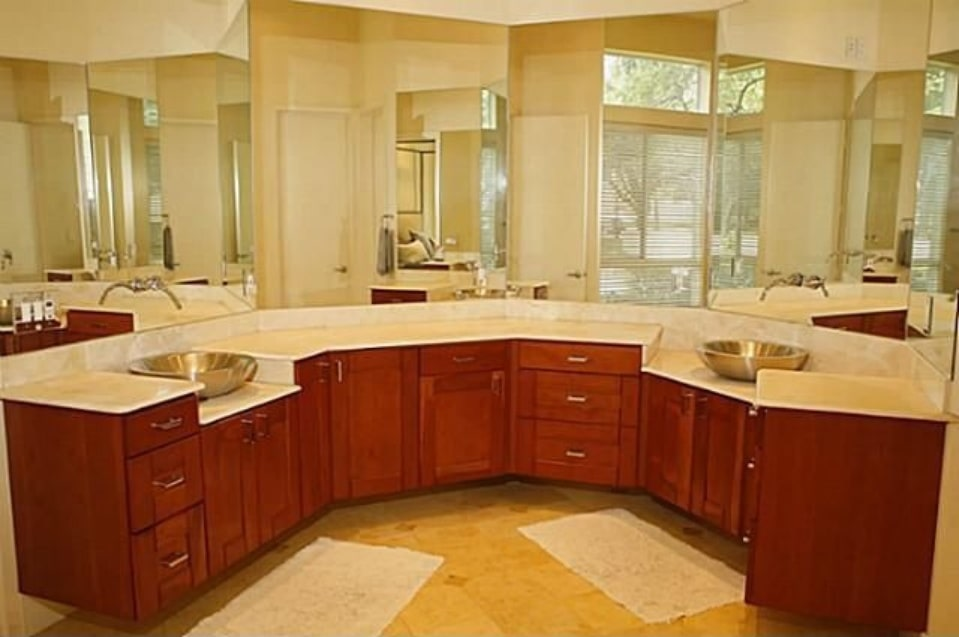 The primary bathroom features a curved vanity with granite countertops and chrome vessel sinks.