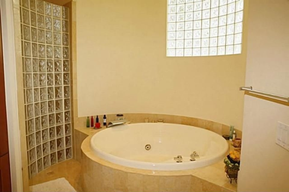 Deep soaking tub complemented by glass block window and divider.