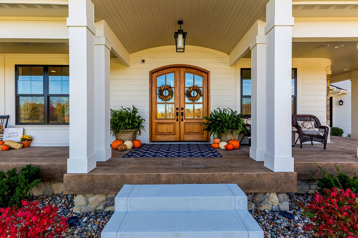 The home entry has a concrete stoop and an arched french front door.