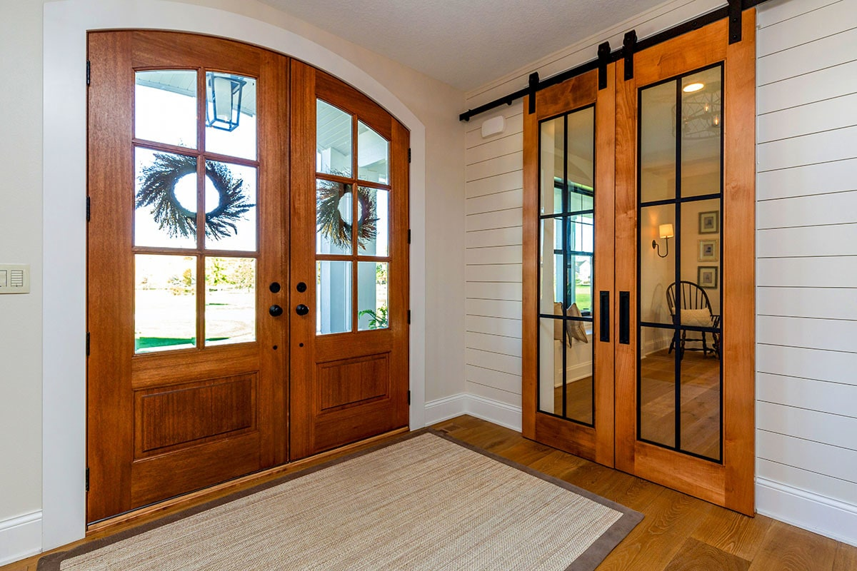 Foyer with double doors and a bordered rug that lays on the natural hardwood flooring.