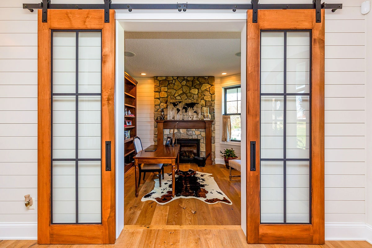 The glass barn door opens to the den with wood furnishings, a cowhide rug, and a stone fireplace.