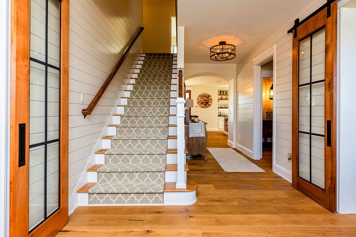 Staircase dressed in a patterned carpet fixed next to a hallway that leads to the kitchen.
