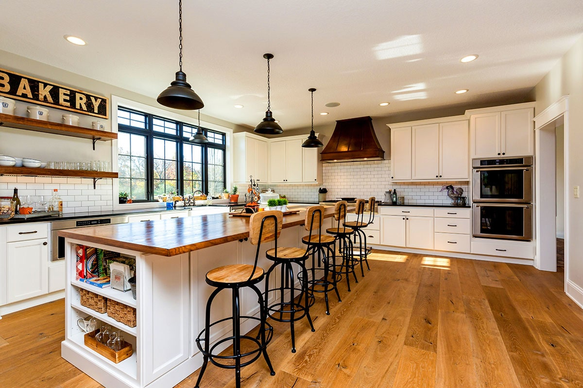 The kitchen is equipped with stainless steel appliances, white cabinetry, subway tile backsplash, and a long center island.
