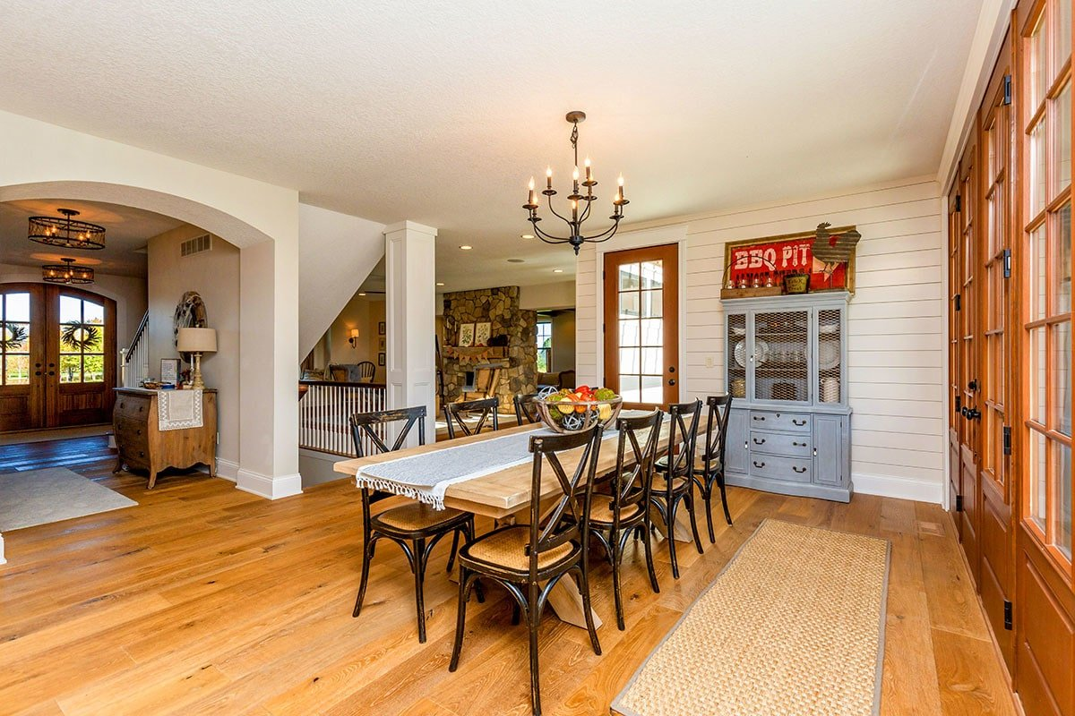 The dining area offers a light blue display cabinet, rectangular dining set, candle chandelier, and a jute runner.