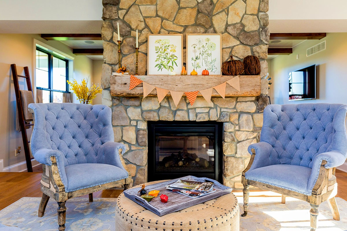 Sitting area with stone fireplace, tufted armchairs, and a round ottoman topped with a distressed tray.