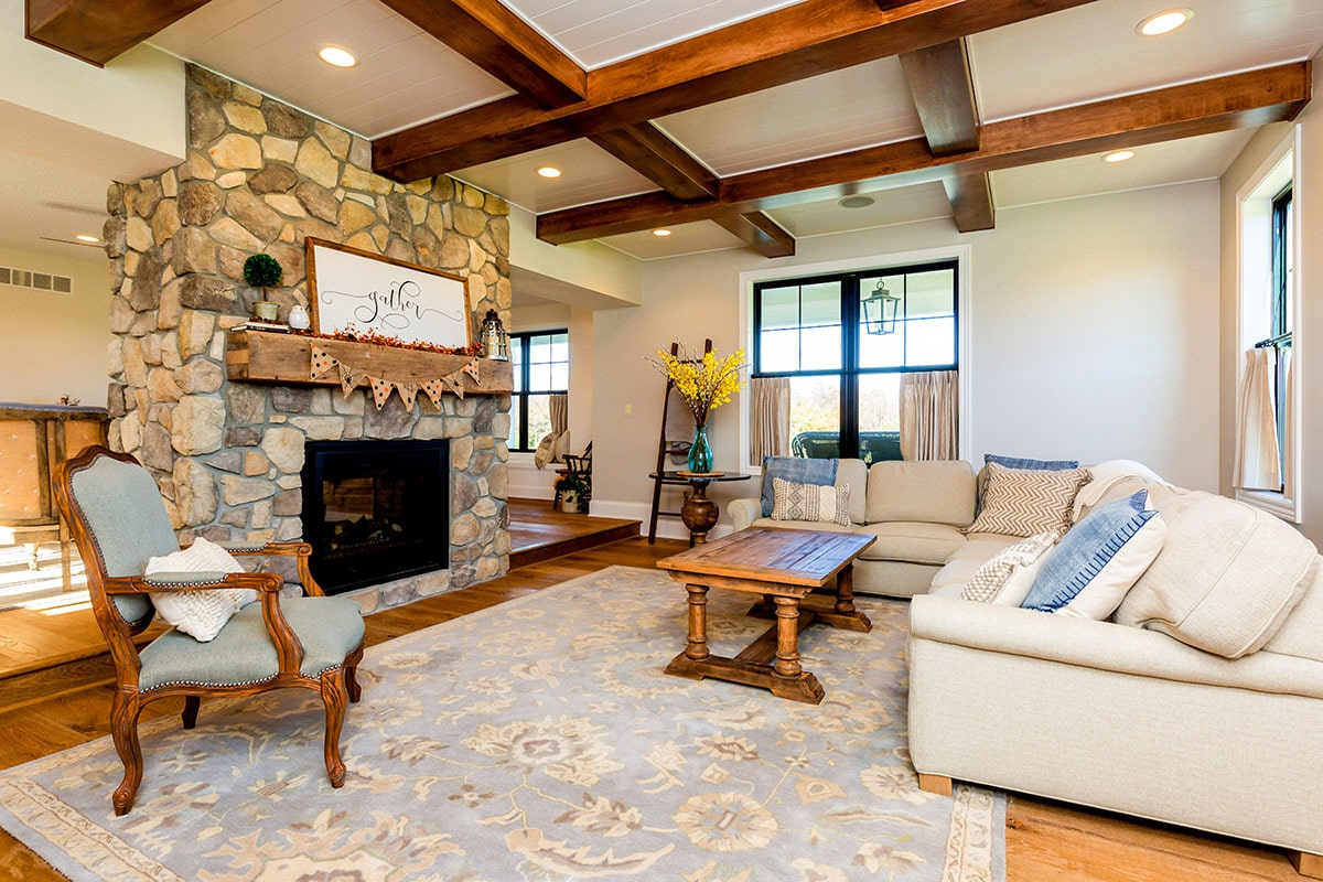 The family room has a coffered ceiling, dual-sided fireplace, L-shaped sofa, cushioned chair, and a wooden coffee table over a floral area rug.