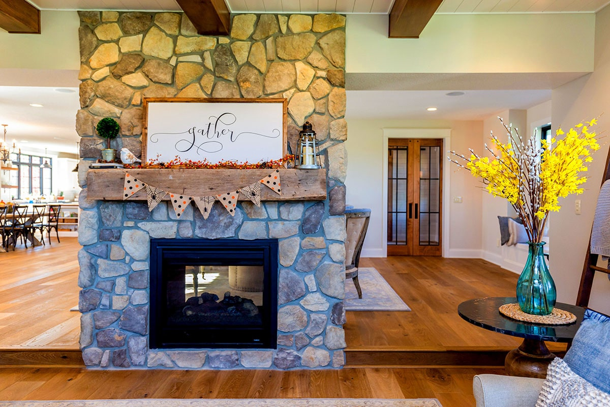 The dual-sided fireplace lined with a wooden mantel is shared by the family room and great room.