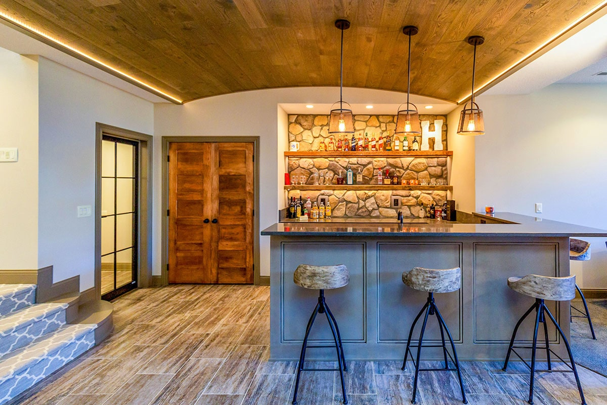 A wet bar under a barrel-vaulted ceiling showcasing a granite top peninsula, round stools, and wooden shelves against a stone wall.