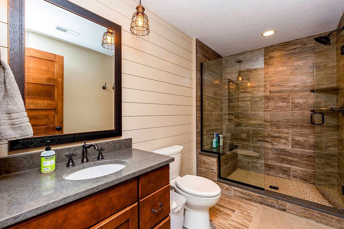 This bathroom has a walk-in shower, a toilet, and a sink vanity paired with a framed mirror.