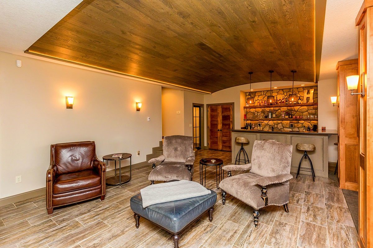 Recreation room with wet bar, warm glass sconces, brown armchairs, and a blue velvet ottoman.