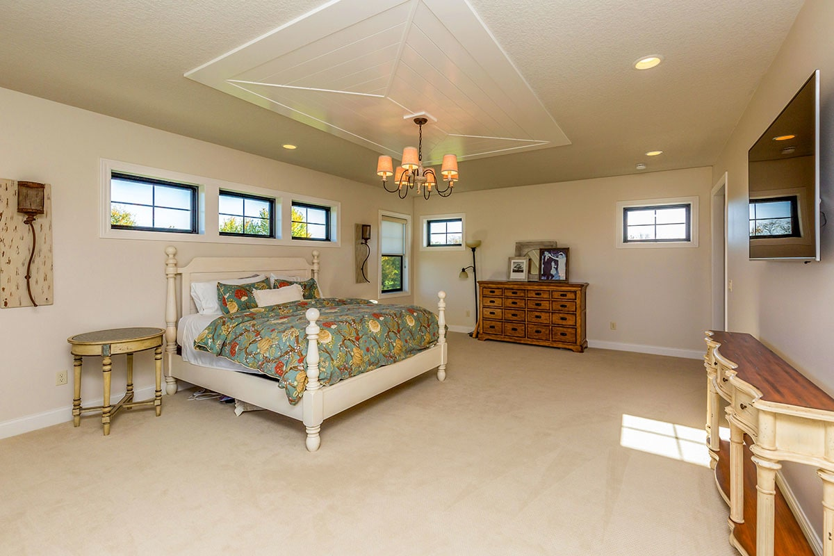 Wrought iron chandelier and recessed ceiling lights create a cozy ambiance on the primary bedroom.