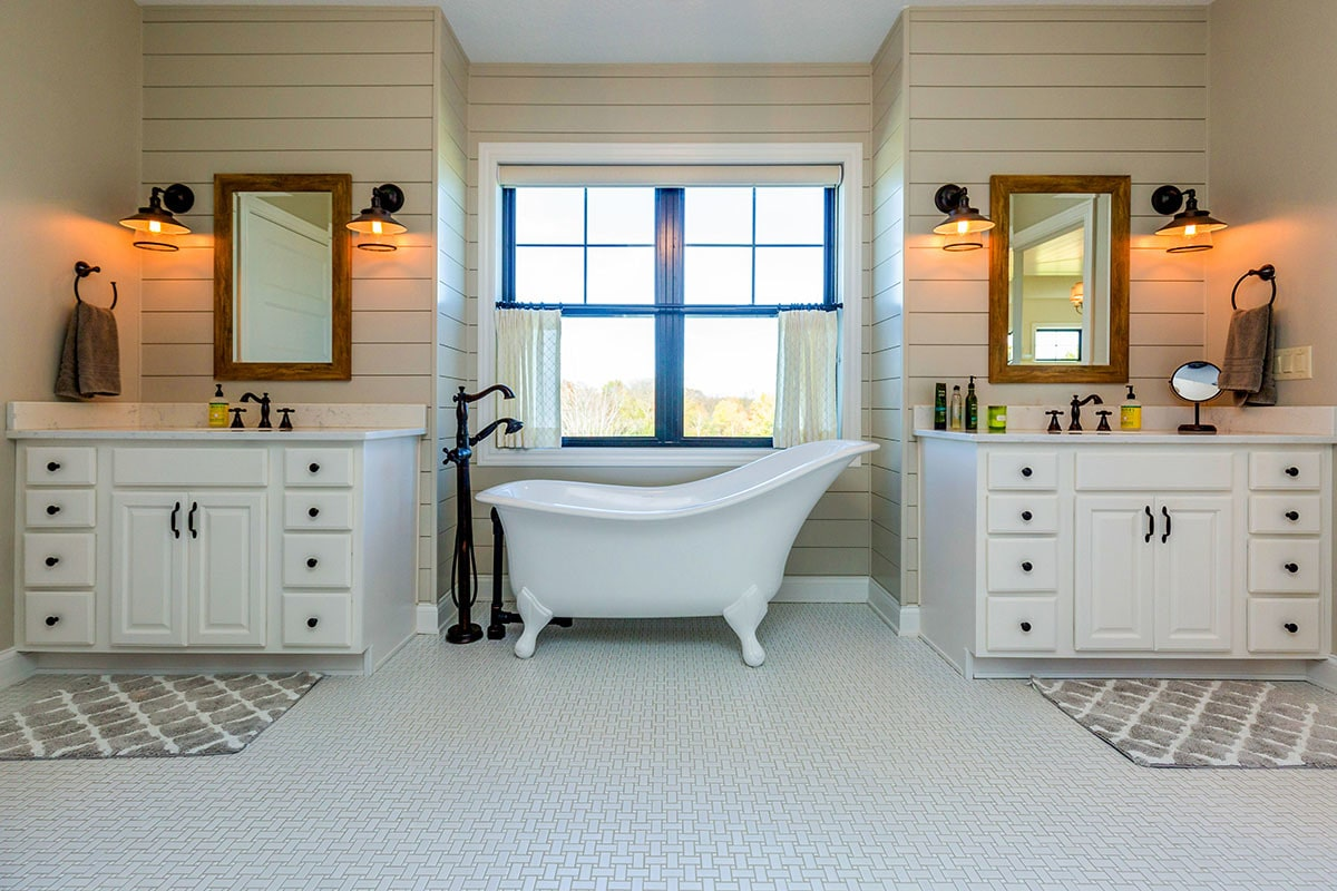 Primary bathroom with his and her vanities along with a clawfoot tub placed in the middle.